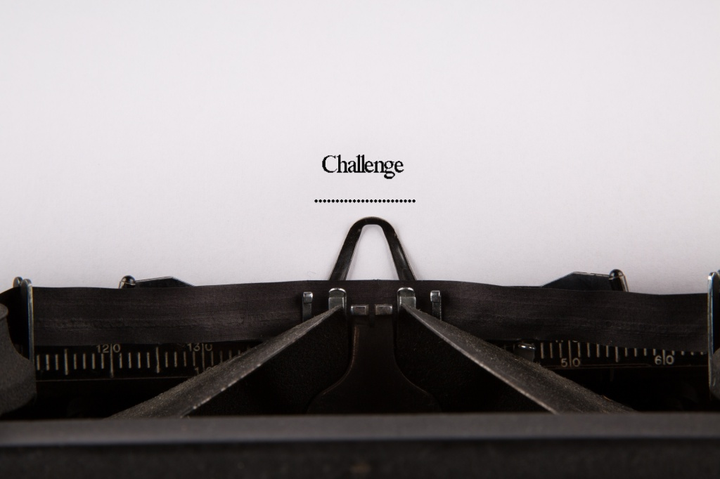 typewriter with paper, the word 'challenge' typed on the paper