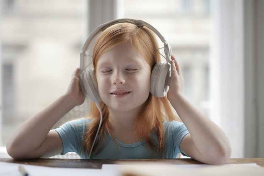 young girl wearing headphones and listening to music