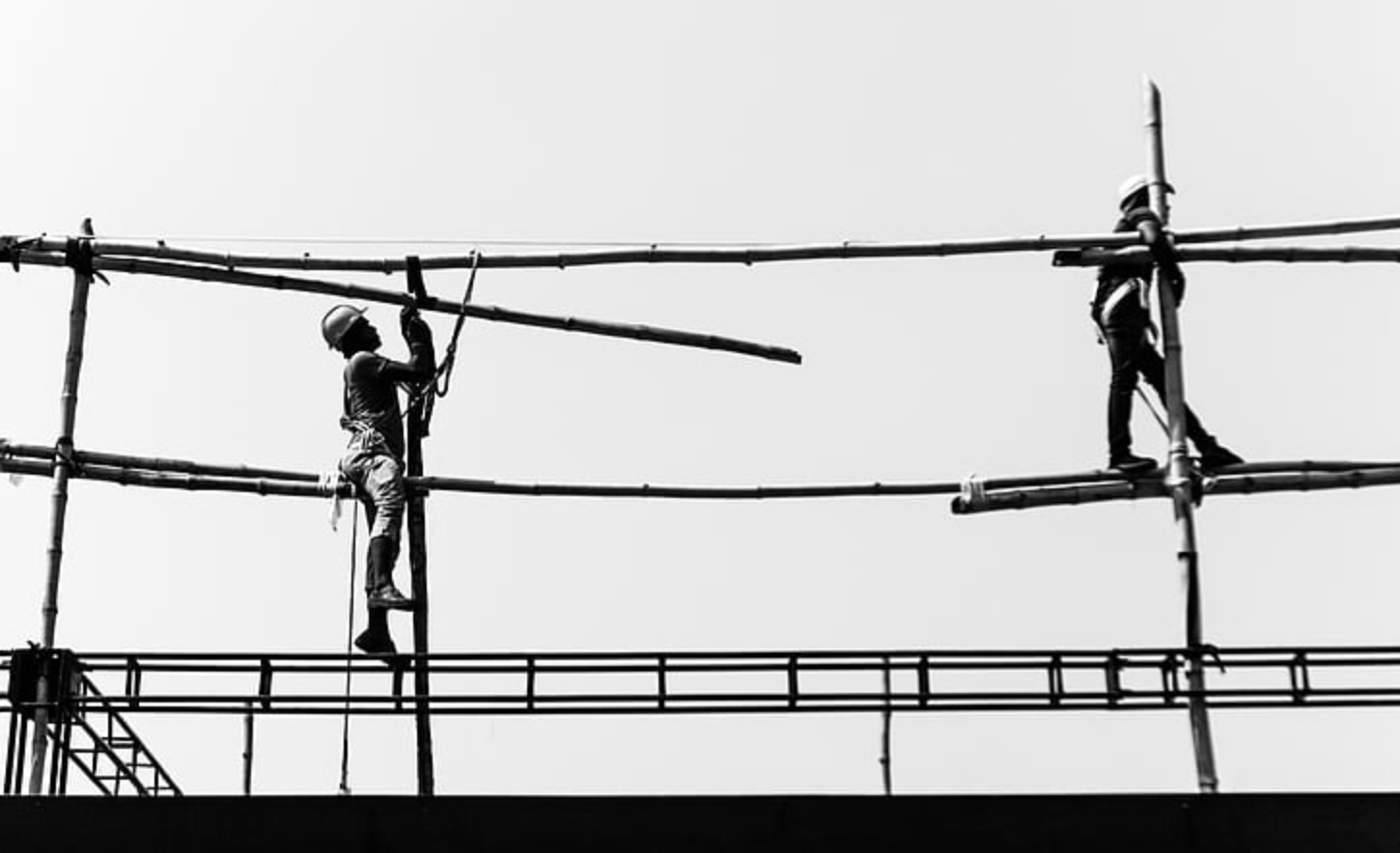 workmen on a building site without scaffolding