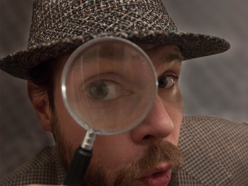 man in tweed with a magnifying glass