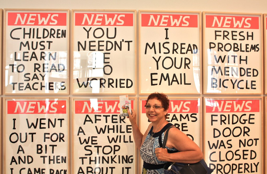 woman standing in front of mocked up newspaper posters