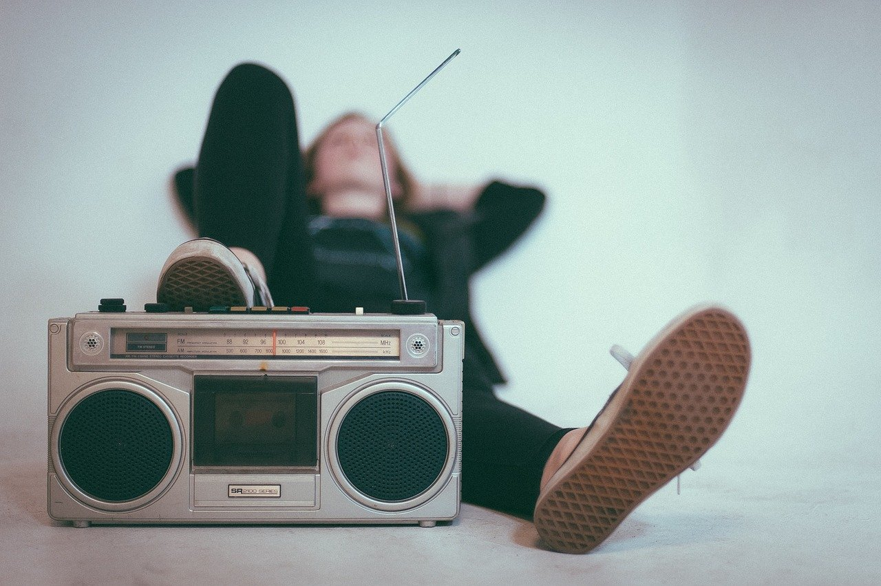 guy reclining listening to an old boombox radio