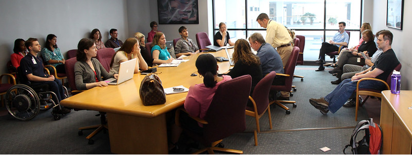 editors around a conference table at a media production meeting, or news conference